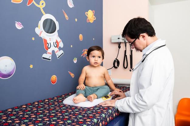 Mittlerer schussdoktor, der ein baby wiegt Kostenlose Fotos
