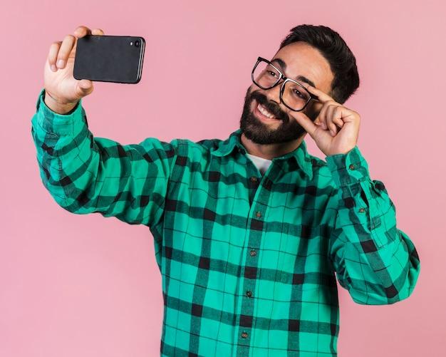 Mittlerer schusskerl, der ein selfie nimmt Kostenlose Fotos
