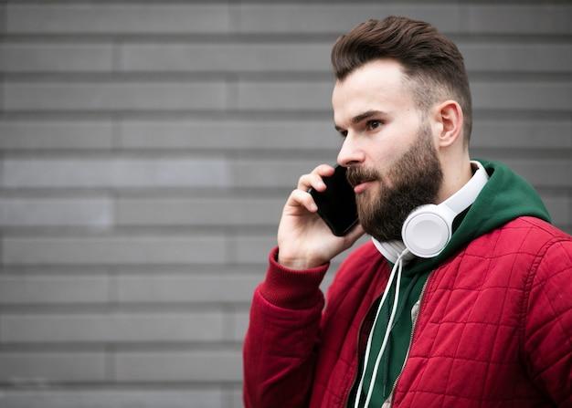 Mittlerer schusskerl mit kopfhörern sprechend am telefon Kostenlose Fotos