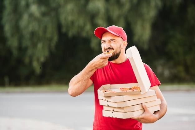 Mittlerer schusslieferer, der pizza isst Kostenlose Fotos
