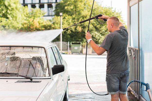 Mittlerer schussmann, der auto mit schlauch wäscht Premium Fotos