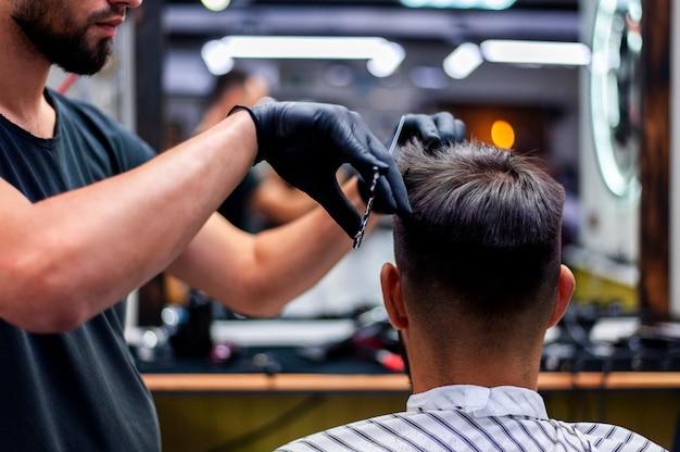 Mittlerer schussmann, der einen haarschnitt erhält Premium Fotos