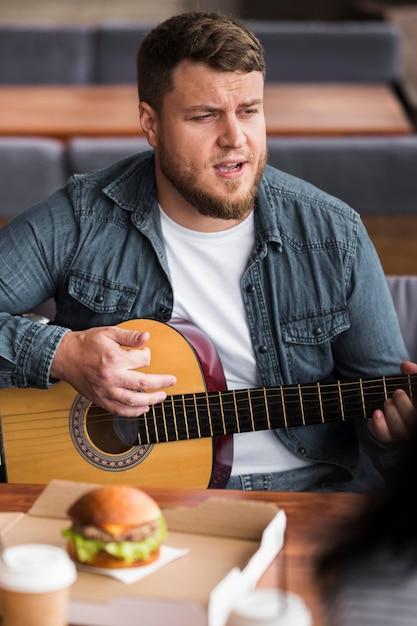 Mittlerer schussmann, der gitarre am tisch spielt Kostenlose Fotos