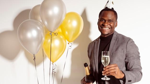 Mittlerer schussmann, der neben luftballons steht Kostenlose Fotos