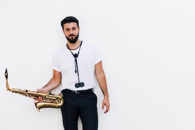 Mittlerer schussmusiker der vorderansicht, der mit saxophon aufwirft Kostenlose Fotos