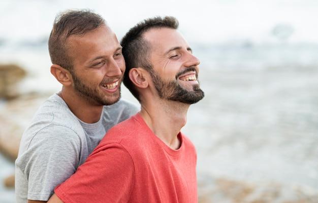 Mittleres schuss glückliches paar am meer Kostenlose Fotos