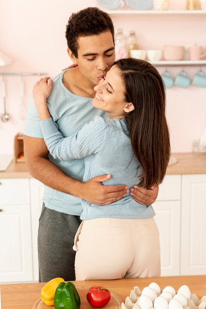 Mittleres schussglückliches paar, das in der küche umarmt Kostenlose Fotos