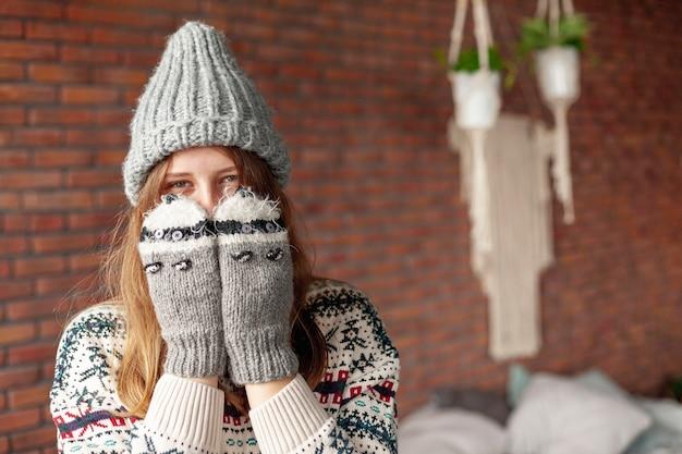 Mittleres schussmädchen, das ihr gesicht mit netten handschuhen bedeckt Kostenlose Fotos