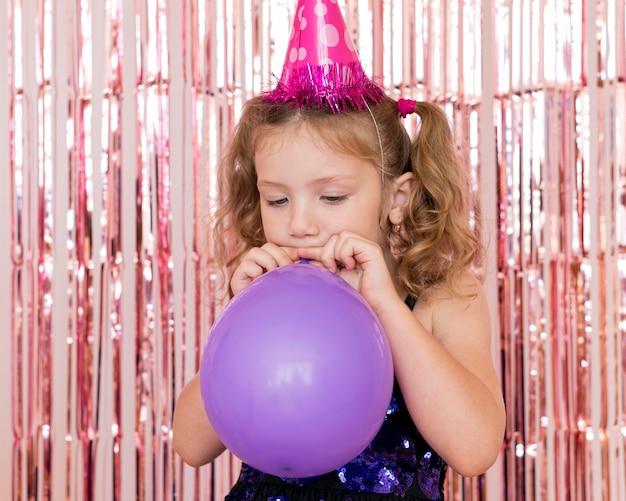 Mittleres schussmädchen, das luftballons aufbläst Kostenlose Fotos
