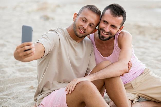 Mittleres schusspaar, das selfies am strand nimmt Kostenlose Fotos