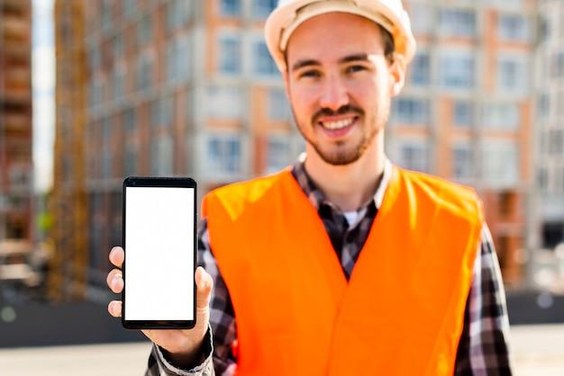 Mittleres schussporträt des bauingenieurs telefon halten Kostenlose Fotos