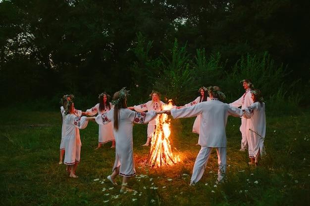Mittsommer tanzen junge leute in slawischem kleiderkreis um ein lagerfeuer im wald. Premium Fotos