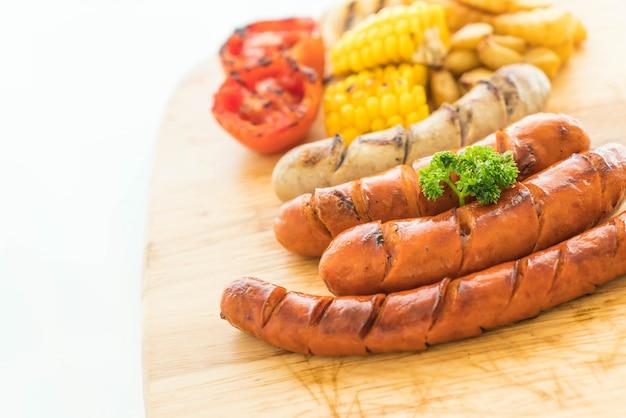 Mix gegrillte wurst mit gemüse und pommes frites Premium Fotos