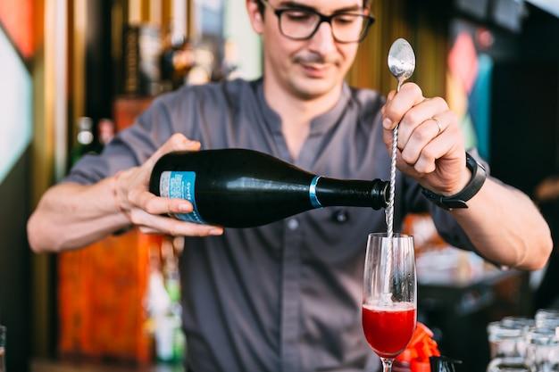Mixologist, der rotes italienisches sodacocktail durch gießen des weins mit langem löffel in trinkglas macht. Premium Fotos