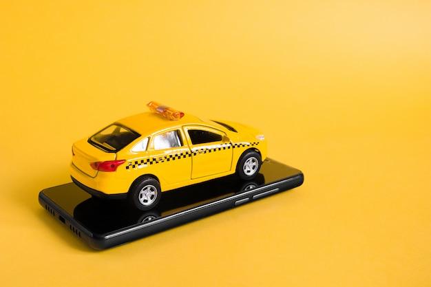 Mobiles online-anwendungskonzept für städtisches taxi. spielzeug gelbes taxi-automodell. hand, die smartphone mit taxiservice-app auf anzeige hält. Premium Fotos
