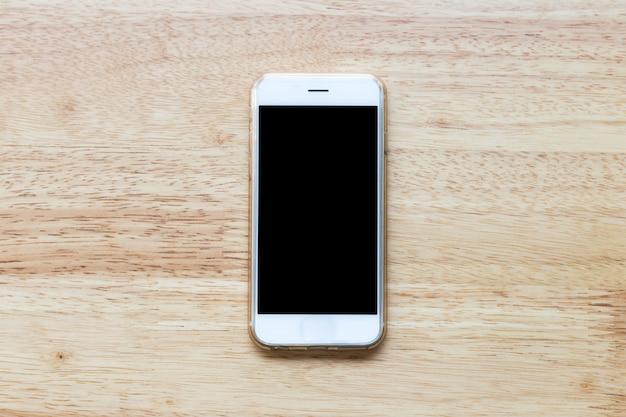 Mobiles weißes telefon des leeren bildschirms auf holztischhintergrund. Premium Fotos