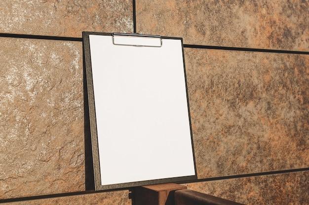 Mock up des tabletts für das papier an der wand Premium Fotos