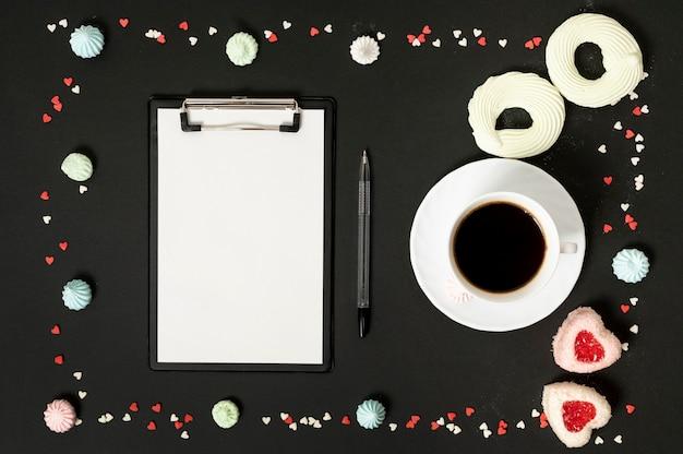 Mock-up-zwischenablage mit tasse kaffee, umgeben von baiser-keksen Kostenlose Fotos