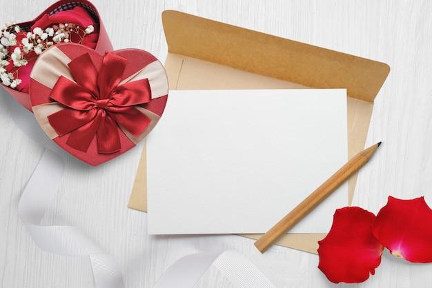 Mockup kraft umschlag und ein brief mit einem herzförmigen geschenk mit einem roten bogen und rosenblättern, grußkarte zum valentinstag mit platz für ihren text. Premium Fotos