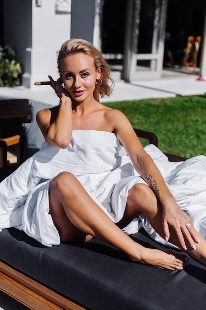 Mode-außenporträt der nackten frau sitzt auf sofa, das sich mit decke bedeckt, die zigarre hält Kostenlose Fotos