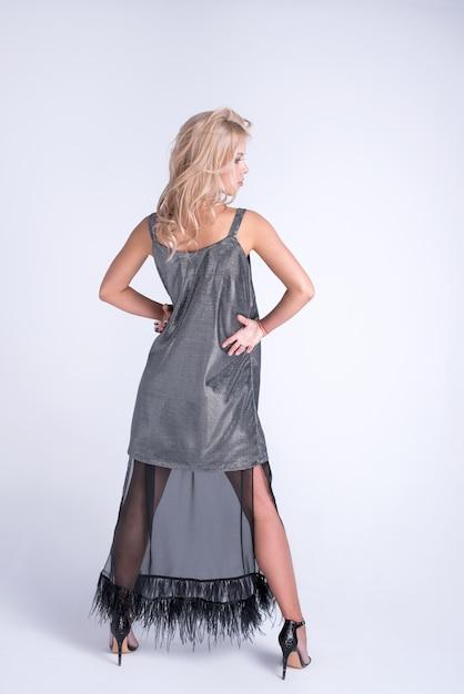 Mode junge frauen im modischen kleid, make-up. stylische wellige frisur, schwarzes outfit. make-up wirft auf grau auf Premium Fotos