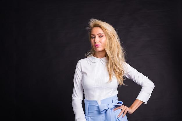 Mode-, porträt- und personenkonzept - junge blonde frau, die über dem schwarzen hintergrund mit steht Premium Fotos