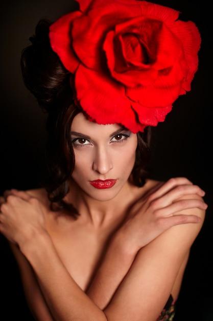 Mode schöne frau mit hellen make-up und roten lippen mit großen roten rose auf dem kopf Kostenlose Fotos