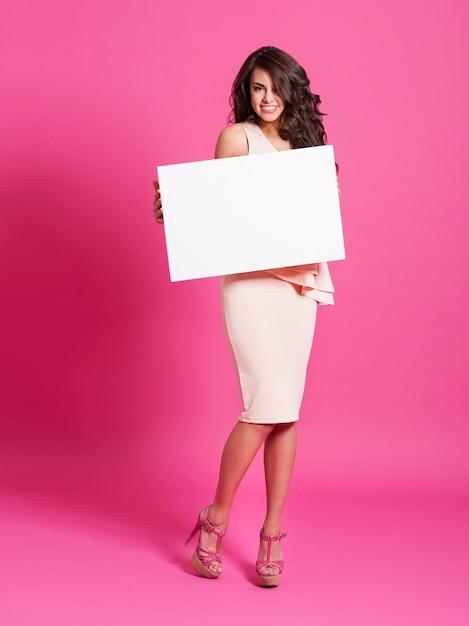 Mode und elegante frau, die whiteboard hält Kostenlose Fotos