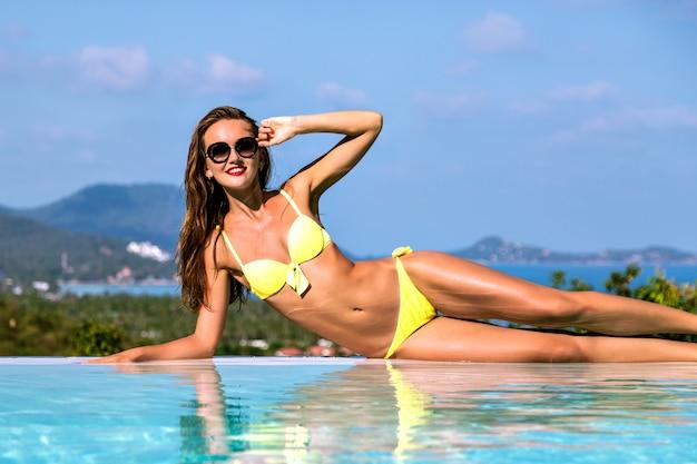 Modebild der atemberaubenden sexy frau mit schlankem körper, der sich nahe infinity-pool entspannt, an exotischer tropischer insel, heißen tagen, bikini, luxusleben, urlaubsstimmung. Kostenlose Fotos
