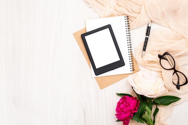 Modeblogger-innenministeriumschreibtisch mit fraueneinzelteilen: moderner ebook leser, papiernotizblock, beige schal, pfingstrosenblumen, gläser Premium Fotos