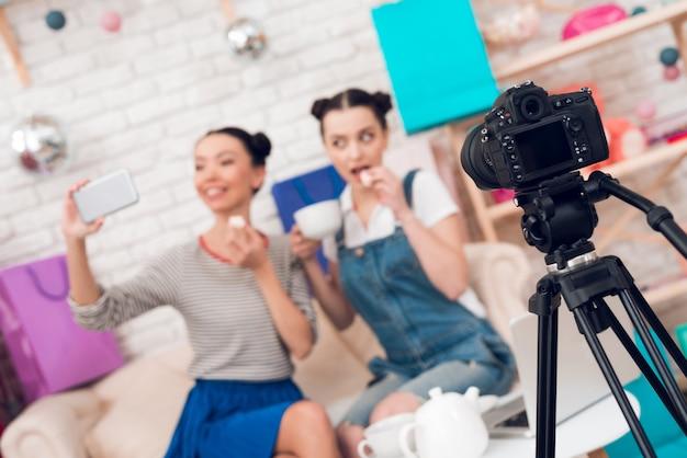 Modebloggermädchen trinken tee zur kamera. Premium Fotos