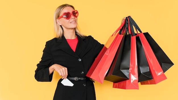 Modedame, die schwarze und herzförmige brille trägt Kostenlose Fotos