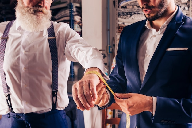 Modedesigner, der das handgelenk des älteren mannes mit gelbem messendem band misst Kostenlose Fotos