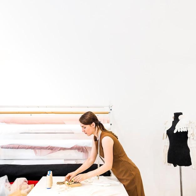 Modedesigner, der gewinde über werktisch wählt Kostenlose Fotos