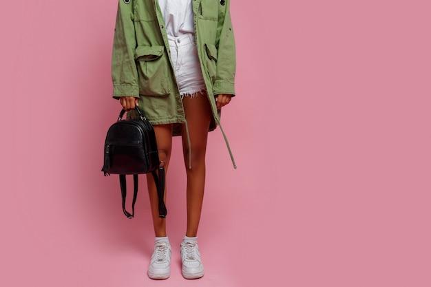 Modedetails. schwarze frau in grüner jacke, weißen shorts und turnschuhen, die auf rosa hintergrund im studio stehen. Kostenlose Fotos