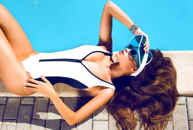 Modefoto des sexy schönen mädchens im schwarzen bikini, der neben einem schwimmbad entspannt, junge hübsche frau mit perfekt gegerbtem körper, der auf gelber luftmatratze im pool liegt und spaß hat Kostenlose Fotos