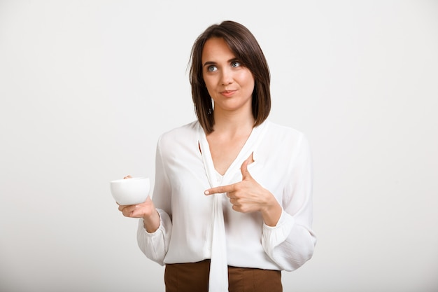 Modefrau trinkt kaffee im büro, sprechen sie mit kollegen Kostenlose Fotos