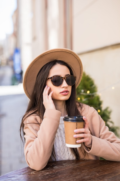 Model lady sitzt auf dem tisch im café kleider in freizeitkleidung dunkle sonnenbrille mit kaffeetasse Kostenlose Fotos