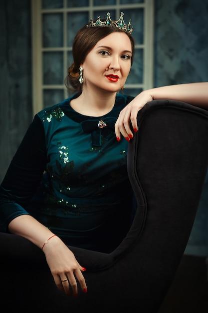 Model posiert in einem dunklen studio als königin Premium Fotos