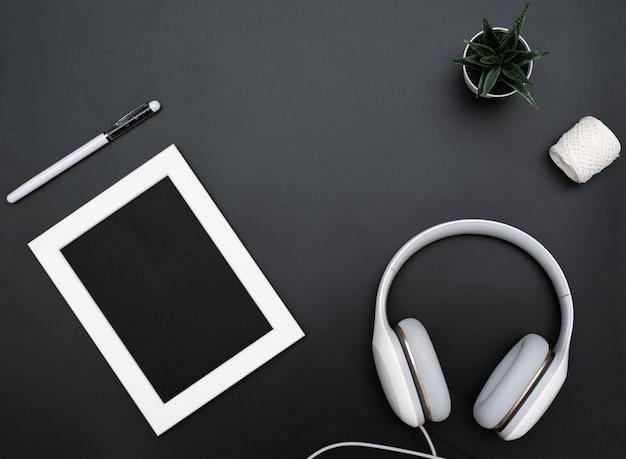 Modell, bilderrahmen, kopfhörer, stift und kaktus objekt auf schwarzem hintergrund schreiben Premium Fotos