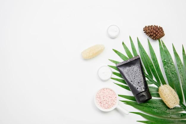 Modell der kosmetischen sahneflasche, des leeren aufkleberpakets und der bestandteile auf einem grünen blatthintergrund. Premium Fotos