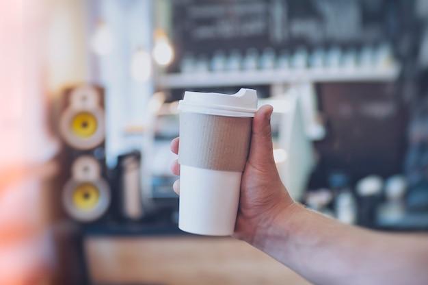 Modell eines pappglases für kaffee in der hand eines mannes vor dem hintergrund einer bar in einem café. Premium Fotos