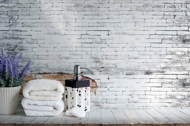 Modell faltete tuch mit seife und houseplant auf holztisch mit alter backsteinmauer Premium Fotos