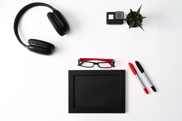Modell, fotorahmen, actionkamera, kopfhörer, brille, stift und kaktus, rotes und schwarzes objekt auf weißem hintergrund Premium Fotos
