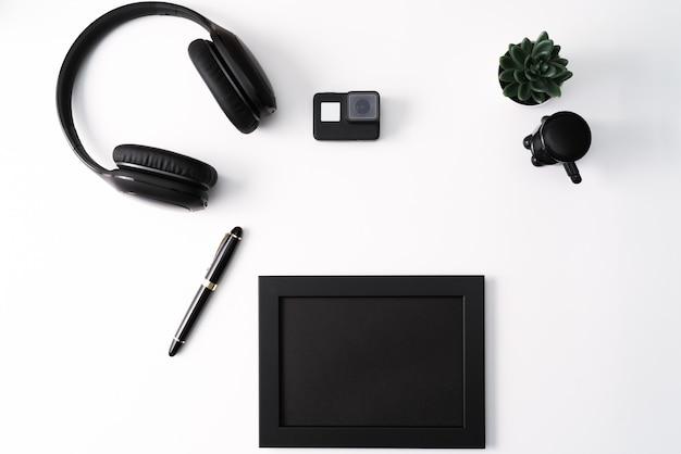 Modell, fotorahmen, aktionskamera, kopfhörer, stift und kaktus, schwarzer gegenstand auf weißem hintergrund Premium Fotos