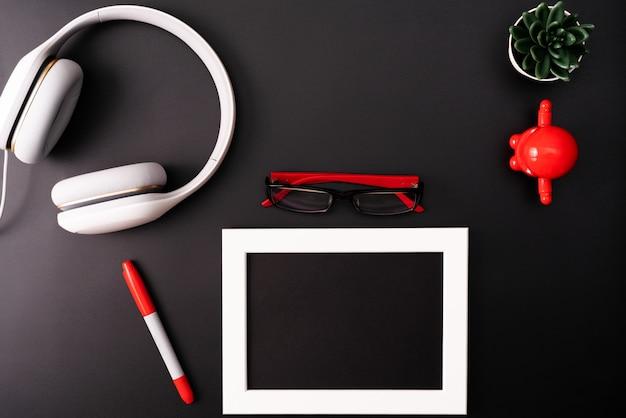Modell, fotorahmen, kopfhörer, brille, stift und kaktus Premium Fotos