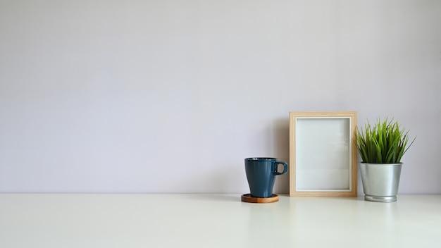 Modell-kopienraumschreibtischfotorahmen und -kaffee mit blumentopf auf weißem schreibtisch. Premium Fotos