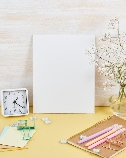 Modell mit leerem weißem rahmen auf gelber tabelle gegen hölzerne wand, warnung, blume im anstarren Premium Fotos