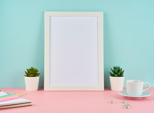 Modell mit leerem weißem rahmen, betriebskaktus, tasse kaffee oder tee auf rosa tabelle gegen blaue wand Premium Fotos