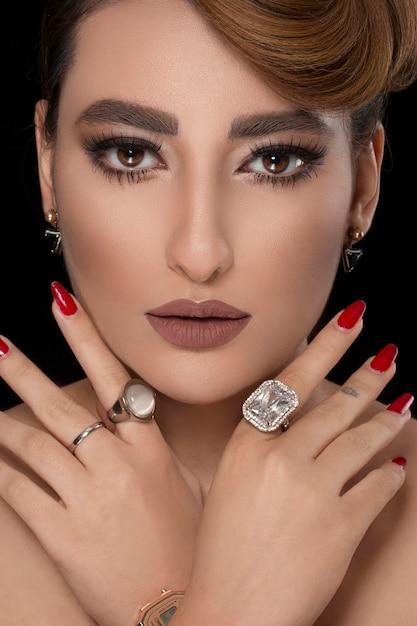 Modell mit partyfrisur und bronze make-up mit diamantschmuck Kostenlose Fotos